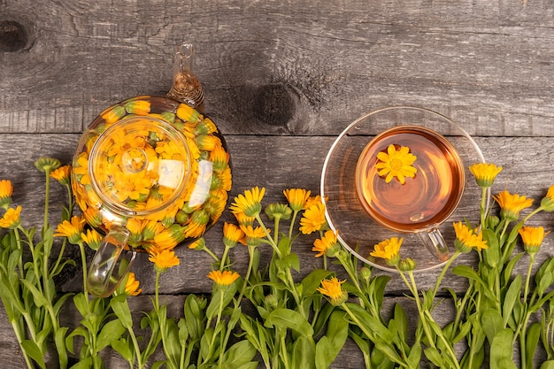Cup of herbal tea and transparent teapot and marigold flowers on wood background. calendula tea benefits your health concept. top view.