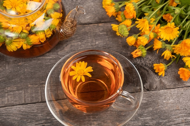 Cup of herbal tea and transparent teapot and marigold flowers on wood background. calendula tea benefits your health concept.