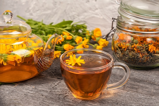 Cup of herbal tea, transparent teapot and marigold flowers on wood background.