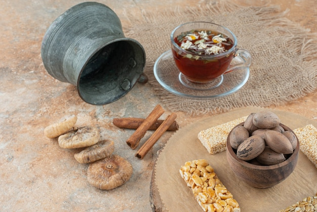 A cup of herbal tea with ancient kettle and peanut brittles