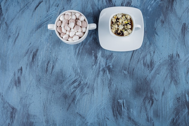Cup of herbal tea with bowl of brown candies on blue background.