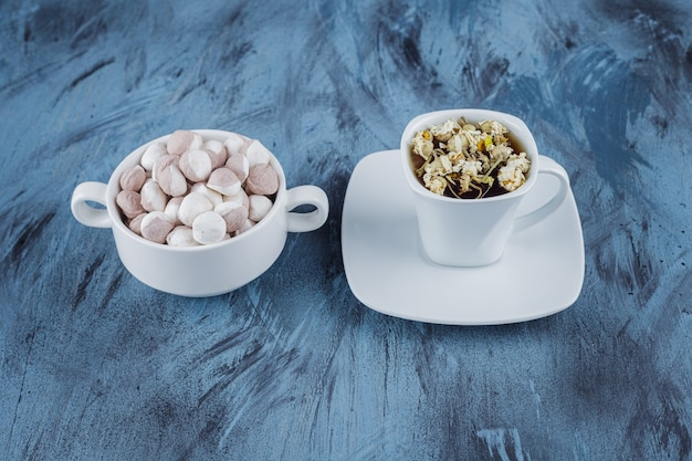 Cup of herbal tea with bowl of brown candies on blue surface.