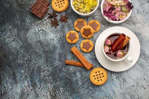 Una tazza di tisana con ciotole di fiori secchi e biscotti e cinnamons su gray