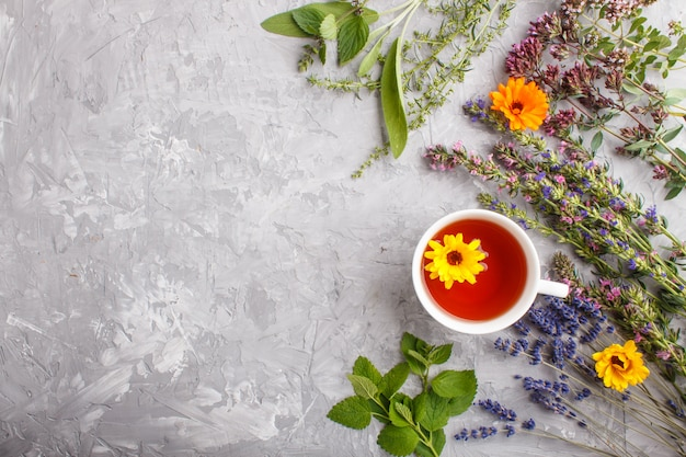 Cup of herbal tea with calendula, lavender, oregano, hyssop, mint and lemon balm. top view, background copyspace.