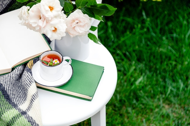 Cup of herbal tea with chamomile and mint on white table outside in garden. romantic leisure breakfast with nature grass background in provence cafe. copy space.
