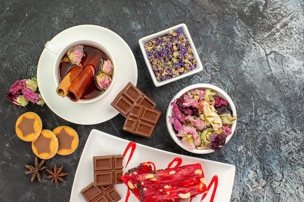 Una tazza di tisana con fiori secchi e biscotti e un piatto di cioccolatini su fondo grigio