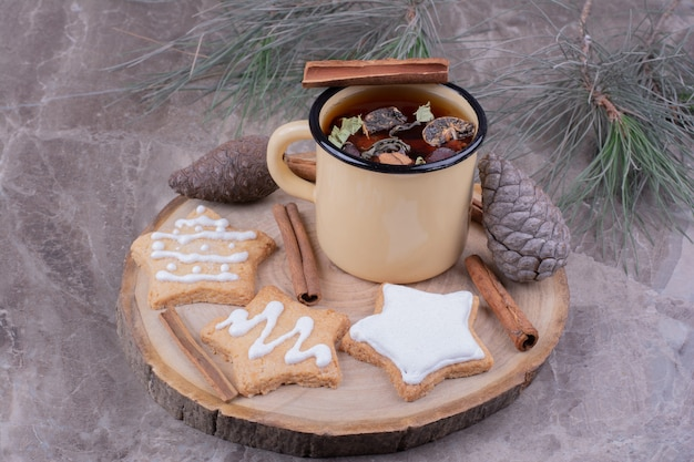 A cup of herbal tea with gingerbreads on a wooden board