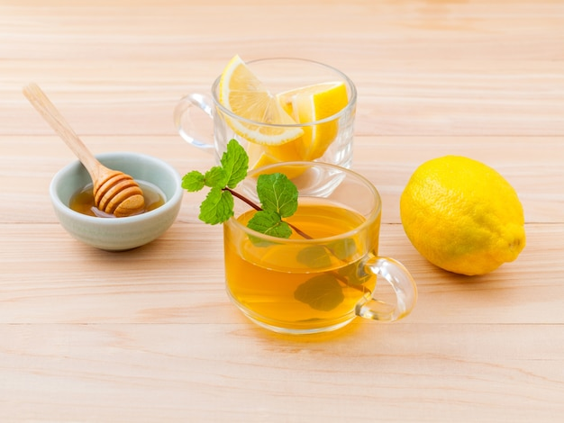 Cup of herbal tea with honey and lemon on wooden background.