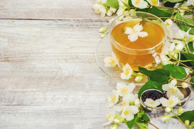 Cup of herbal tea with jasmine flowers. selective focus.