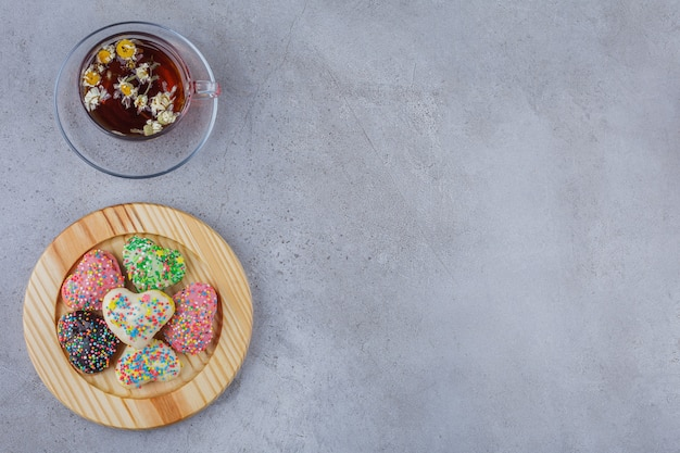 Cup of herbal tea with plate of sweet cookies on stone.