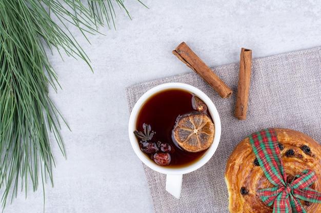 Tazza di tisana con rotolo di uvetta sulla tovaglia. foto di alta qualità