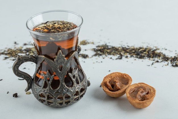 A cup of herbal tea with sweet walnut shaped cookie.