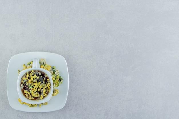 Tazza di tisana con fiori gialli. Foto Gratuite