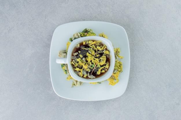 Tazza di tisana con fiori gialli