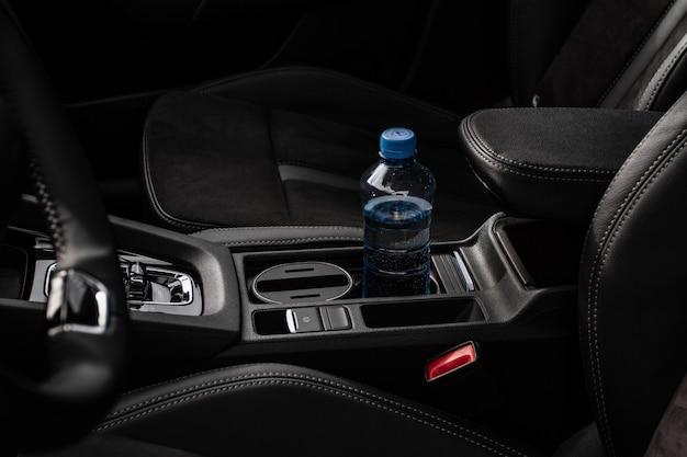 モダンな車内のカップホルダー。現代の車の内部ビュー。カーカップホルダーにボトルを置きます。