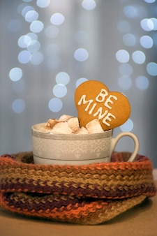 Cup of hot and aromatic coffee with marshmallow and heart cookie with be mine phrase on blue fairy lights