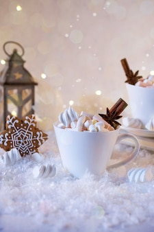 Cup of hot beverage with marshmallow and spices on snow .