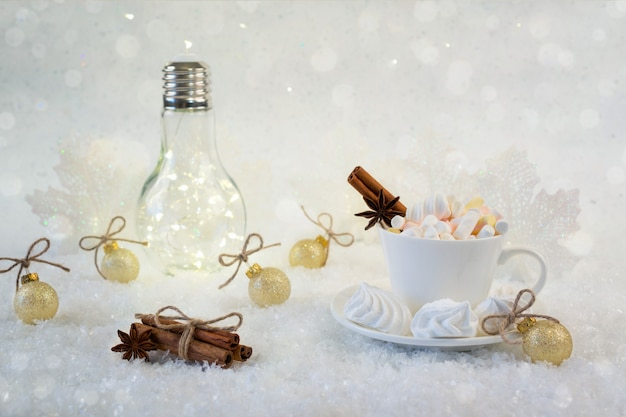 Cup of hot beverage with marshmallow and spices on snow