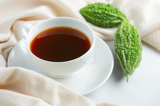 Una tazza di tè caldo alla zucca amara con una zucca amara cruda sul pavimento di marmo bianco