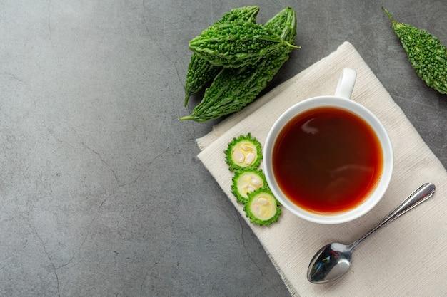 Una tazza di tè caldo zucca amara con posto zucca amara a fette crudo su tessuto bianco
