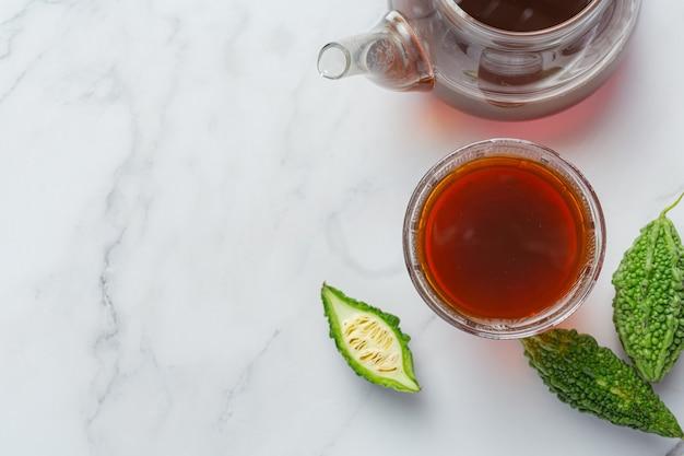 Una tazza di tè caldo zucca amara con zucca amara affettata cruda sul pavimento di marmo bianco