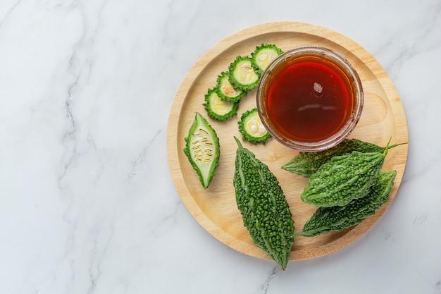 Una tazza di tè caldo zucca amara con zucca amara affettata cruda sul piatto di legno