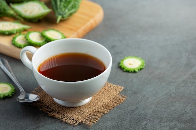 Una tazza di tè caldo alla zucca amara con una zucca amara cruda a fette sul pavimento scuro
