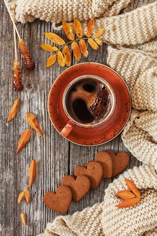 Cup of hot black coffee and heart-shaped gingerbread with autumnal leaves and warm scarf.