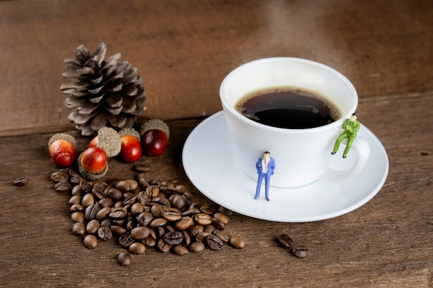 A cup of hot, black coffee is on wooden table, decorate with coffee bean and small figure model.
