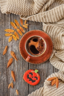 Cup of hot black coffee and pumpkin shaped gingerbread with autumnal leaves and warm scarf.