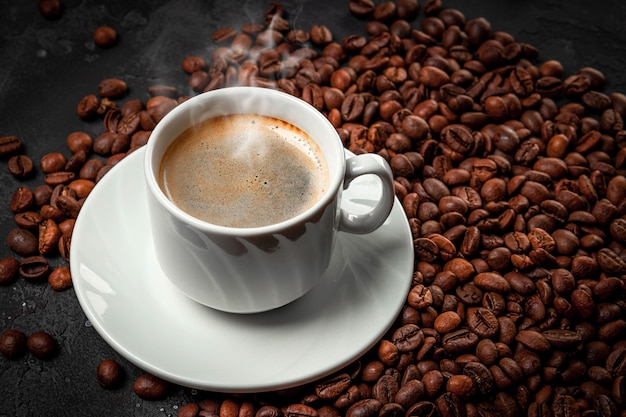 Cup of hot black coffee and roasted coffee beans close up.