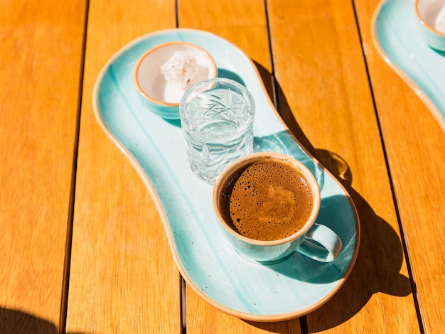 A cup of hot black turkish coffee in blue cup served with glass of water and sugar