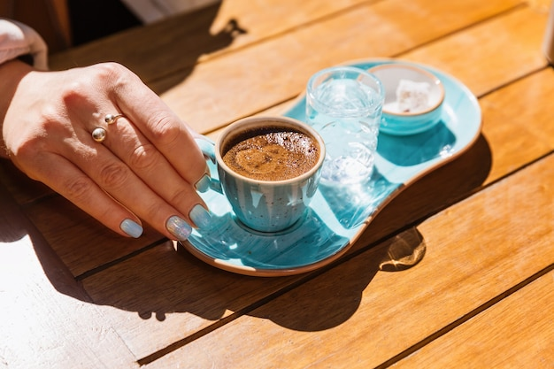 A cup of hot black turkish coffee in blue cup in women's hands served with glass of water and sugar