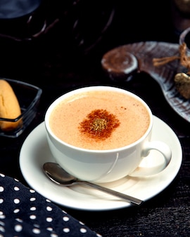 Cup of hot cappuccino with cinnamon