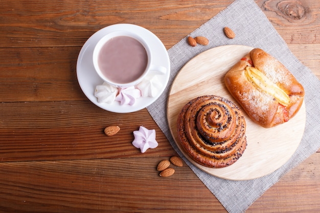 A cup of hot chocolate and buns  on brown wooden background.