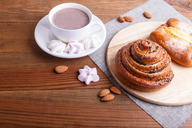 A cup of hot chocolate and buns  on brown wooden surface.