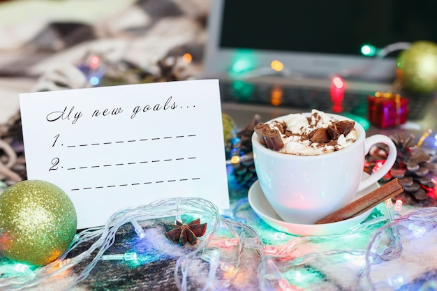 A cup of hot chocolate and marshmallows in christmas decoration. new year goals list.