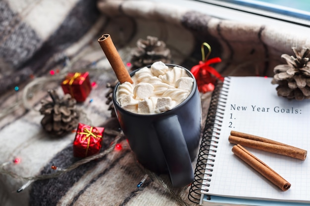 A cup of hot chocolate and marshmallows on the window. new year goals with blank list.