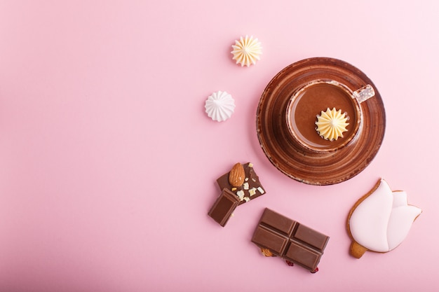 Cup of hot chocolate and pieces of milk chocolate with almonds on pink background. top view.