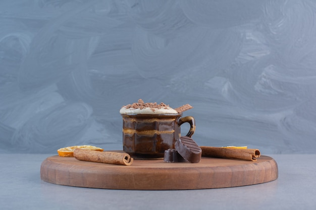 Cup of hot chocolate and tasty snacks on wooden board.