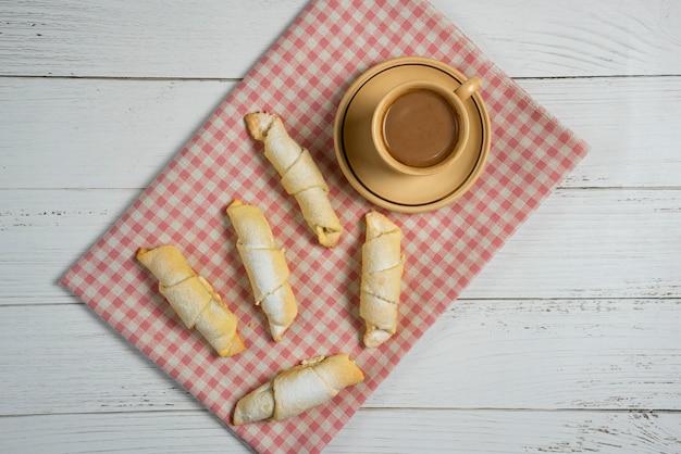Una tazza di cioccolata calda con pasticcini mutaki tradizionali caucasici sull'asciugamano controllato