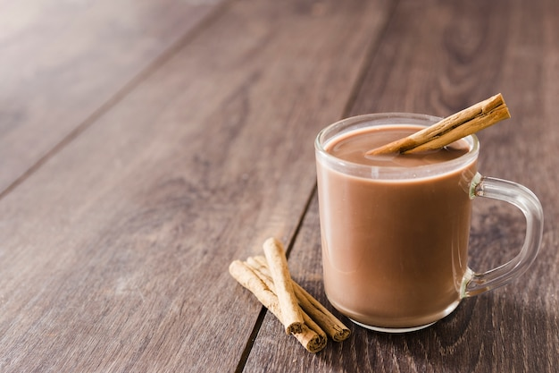 Cup of hot chocolate with cinnamon sticks and copy space