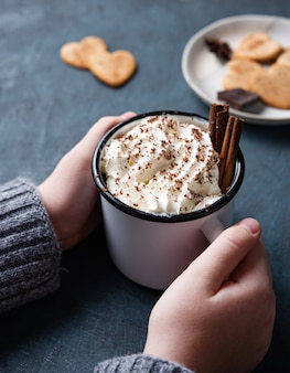 A cup of hot chocolate with cream and cinnamon  in  woman hand on a dark  table with homemade cookies. top view and close up