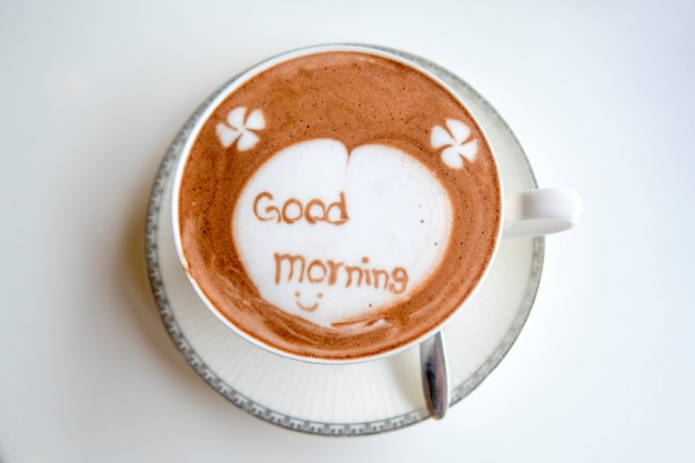 "Cup of hot chocolate with ""good morning"" message on white table background."