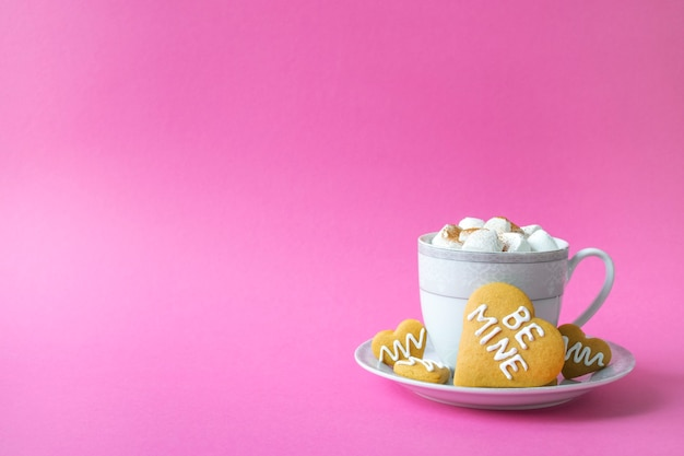 Cup of hot chocolate with marshmallow and biscuit in heart shape with be mine phrase on pink