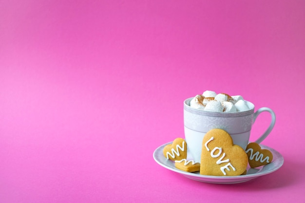 Cup of hot chocolate with marshmallow and cookie in heart shape with love phrase on pink background. festive coffee serving for romantic breakfast on valentines day. greeting card with copy space.