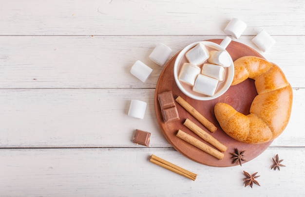 A cup of hot chocolate with marshmallow, croissant and spices on white wooden background.