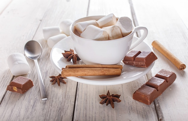 A cup of hot chocolate with marshmallow and spices on white wooden background. close up.