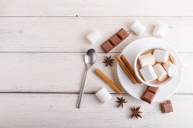 A cup of hot chocolate with marshmallow and spices on white wooden background.