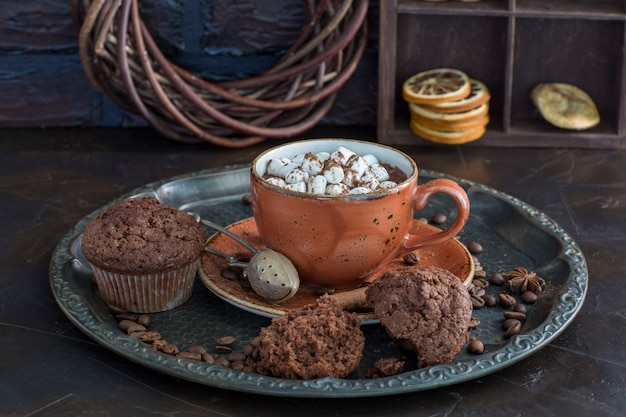 A cup of hot chocolate with marshmallows and muffins close up